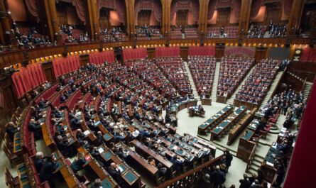 Poslanecká sněmovna plná hlasujících politiků.