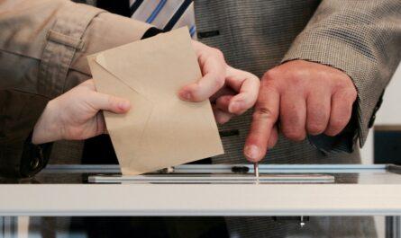 Muž ukazuje na volební urnu, která možná rozhodně volby.